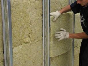 Процесс укладки минеральной ваты между металлическим каркасом