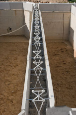 Противоположные стороны блока несъемной опалубки сцепляются между собой пластиковыми стяжками, одеваемыми на ввинченные стальные крюки.